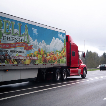 a truck with advertising on the side on a highway